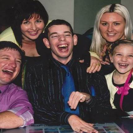 Group of family and friends surrounding disabled young man, all laughing