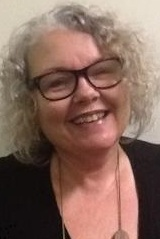 photo of ann greer.  A woman with glasses and grey hair smiling broadly