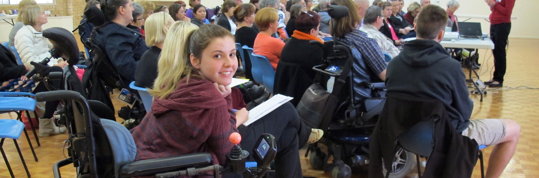 Smiling young lady in a wheelchair at an event