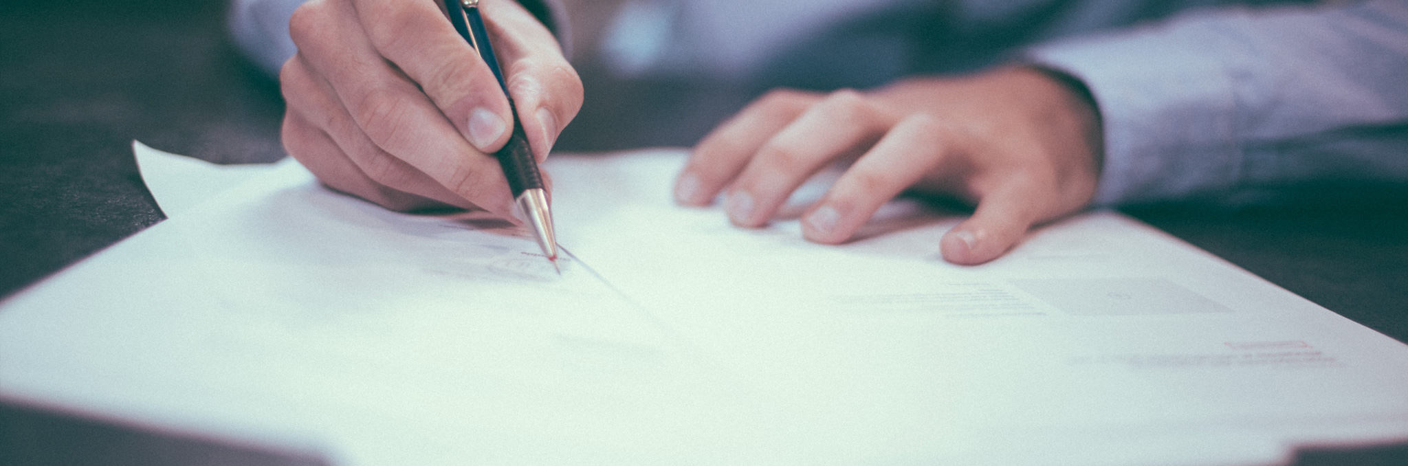 Person signing documents. Photo by Helloquence on Unsplash