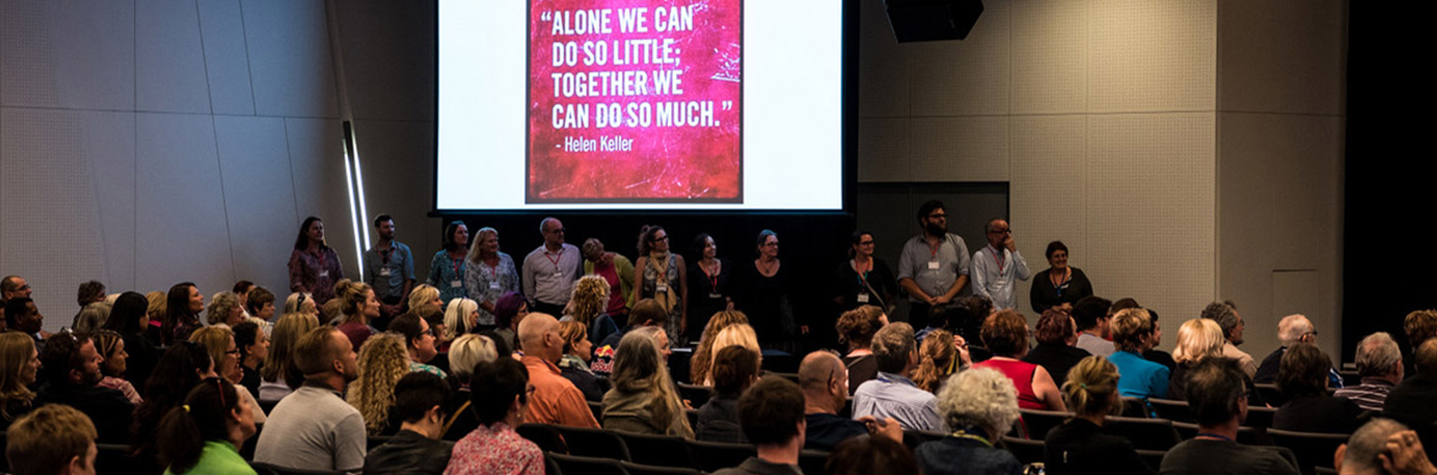 cru board and staff standing in line at the front of a conference under a slide that reads 'alone we can do so little, together we can do so much' by Helen Keller