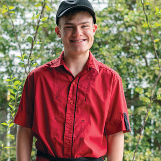 Boy with down syndrome in workers uniform