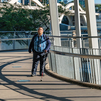 Blind man with white cane walks along bridge