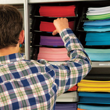 Picture of a man standing in front of a shelf full of stacks of different coloured papers