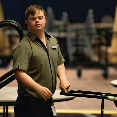 Photograph of man with down syndrome in work uniform