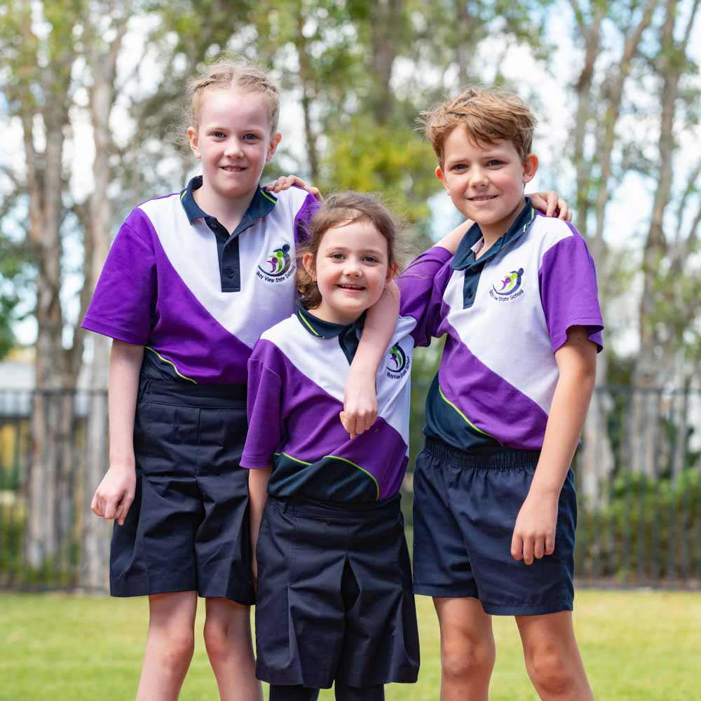 Three young kids in school uniform with their arms over each others shoulders