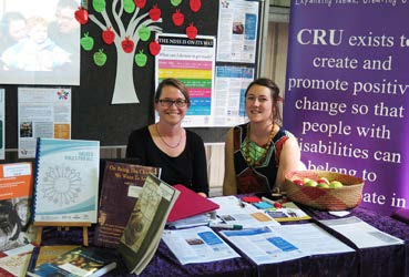 Two ladies smiling surrounded by CRU resourses