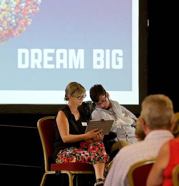Presentation to a room with a screen in the background that says Dream Big