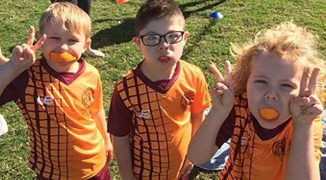 Three children in orange sports tops with orange segments in their mouths