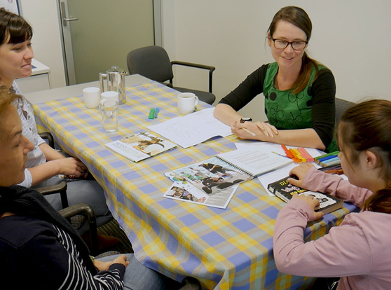 4 women sitting at a table with planning resources and cru materials.  1 woman has a disability, 1 is a staff member from cru and the other 2 are her supporters
