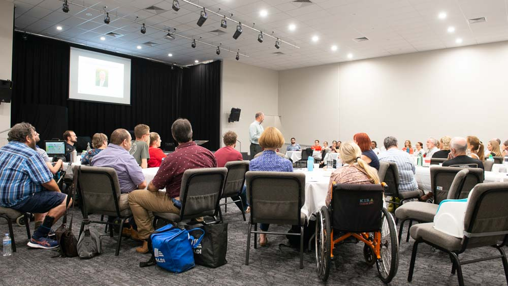 A diverse group of people, some in wheelchairs, sitting around tables and watching a man present